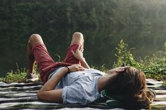 Man relaxing by a lake in the forest Stock Photography