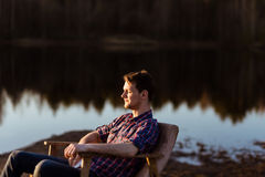 Man relaxing by a lake. In Forest. Rest of Hipster Freelancer Stock Images