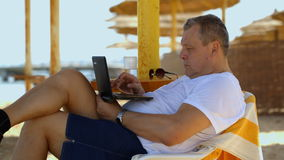 Man relaxing with a laptop at beach resort. Man relaxing with a laptop at a beach resort reclining on a comfortable chair under a straw beach umbrella staring stock footage