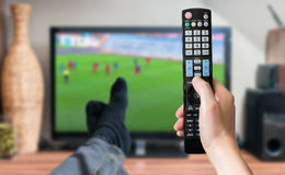 Man is relaxing with legs on table and is watching football match on tv. Royalty Free Stock Photo