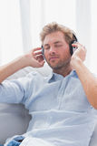 Man relaxing while listening to music on a couch Stock Image