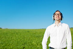 Man relaxing listening to music in a field Stock Photos