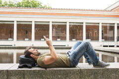 Man relaxing and looking tablet computer in the street. Royalty Free Stock Photo