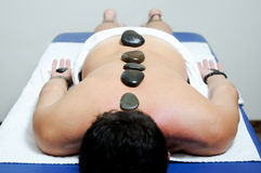 Man relaxing on massage bed with hot stones Stock Photos
