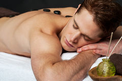 Man relaxing on a massage bed with hot stones. Relaxing young guy with hot stones on his back Stock Photos