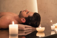 Man relaxing on massage table at Asian spa and wellness center. Young man relaxing on massage table surrounded by scented candles at Asian spa and wellness Stock Image