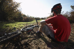 Man Relaxing Beside Mountain Bike In Countryside Royalty Free Stock Photography