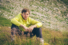 Man relaxing in mountains sitting on grass valley Traveling hiking Royalty Free Stock Images