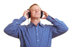 Man relaxing with music. Elderly man listening to music with headphones Royalty Free Stock Photo