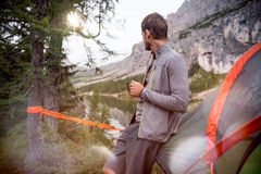 Man relaxing near hanging tent camping with hot beverage looking at lake panorama.Group of friends people summer. Adventure journey in mountain nature outdoors Stock Photo