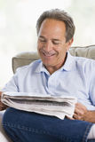 Man relaxing with a newspaper smiling Royalty Free Stock Photo