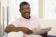 Man relaxing with a newspaper smiling Stock Photo