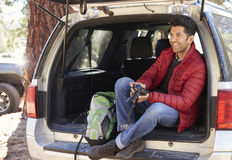 Man relaxing in open back of car holding camera Royalty Free Stock Photos