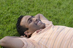 Man relaxing outdoors looking happy and smiling Royalty Free Stock Image