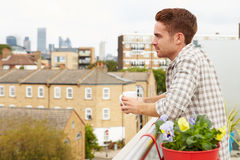 Man Relaxing Outdoors On Rooftop Garden Drinking Coffee Royalty Free Stock Photo