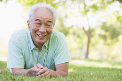 Man relaxing outdoors smiling. Man relaxing outdoors on the grass smiling stock photos
