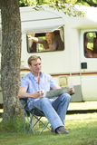 Man Relaxing Outside Mobile Home On Vacation Stock Image