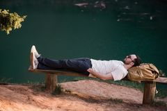 Man Relaxing Outside. Wearing a white T shirt, dark pants, sunglasses, a young guy is lying down on wooden bench against. Lake in a forest outdoors Royalty Free Stock Image