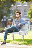 Man Relaxing On Park Bench With Takeaway Coffee Royalty Free Stock Images