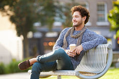 Man Relaxing On Park Bench With Takeaway Coffee. Man Relaxing Outdoors On Park Bench With Takeaway Coffee Looking Into Distance royalty free stock image