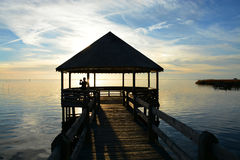 Man relaxing on pier on the lake at sunset. Stock Photography