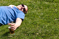 Man relaxing with pint of beer. Man in sunglasses relaxing on grass with pint of beer or larger, summer scene with copy space royalty free stock image