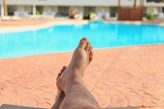 Man relaxing by the pool stock images