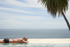 Man Relaxing By Poolside At Resort. Young African American man relaxing by poolside with ocean in background Stock Photos