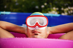 Man relaxing in a portable swimming pool Royalty Free Stock Photography