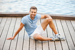 Man relaxing on quayside. Handsome young man smiling and looking at camera while relaxing on quayside Stock Photos