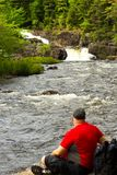 Man relaxing by the rapids Royalty Free Stock Photography
