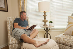 Man relaxing and reading a book. Man relaxes while reading a book and looks out the window stock photo