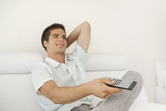 Man Relaxing with Remote Control Stock Photo