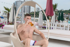 Man Relaxing on Resort Patio with Glass of Beer Royalty Free Stock Photography