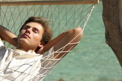 Man relaxing resting on a hammock on vacation. With a turquoise sea in the background stock photos