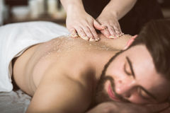 Man relaxing during a salt scrub beauty therapy Stock Photos