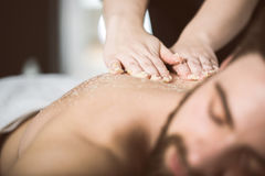 Man relaxing during a salt scrub beauty therapy Stock Photography