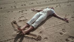 Man relaxing on sand. Man making angel on sand. Man lying on sand stock video footage