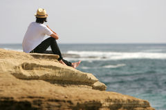Man relaxing at the seaside. Sitting on cliff near the sea Royalty Free Stock Images