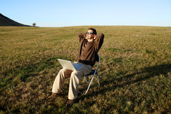 Man relaxing sitting in field with laptop Stock Photos