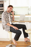 Man Relaxing Sitting In Kitchen Talking On Phone Royalty Free Stock Photos