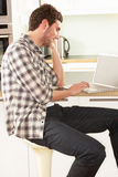Man Relaxing Sitting In Kitchen Talking On Phone Stock Photography