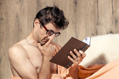 Man relaxing on sofa couch reading novel story book Royalty Free Stock Image
