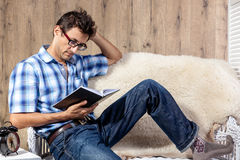 Man relaxing on sofa couch reading novel story book Stock Images