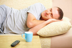 Man relaxing on sofa with cup Royalty Free Stock Photos