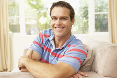 Man Relaxing On Sofa At Home Stock Photos