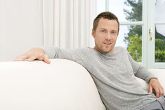 Man relaxing on sofa at home. Royalty Free Stock Photos