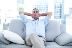Man relaxing on sofa at home. High angle view of man relaxing on sofa st home royalty free stock photos