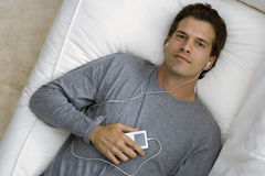Man relaxing on sofa at home, listening to MP3 player, smiling, portrait, overhead view Stock Photo