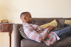 Man Relaxing On Sofa At Home Using Laptop royalty free stock images